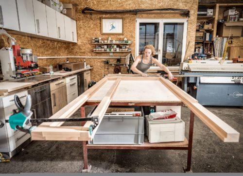 Hier sieht man Schreinermeisterin Maxime Krämer, wie sie an einem großem Möbelstück arbeitet.